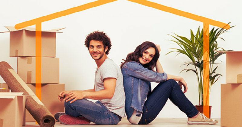 Young couple sitting on the ground while surrounded by cardboard boxes
