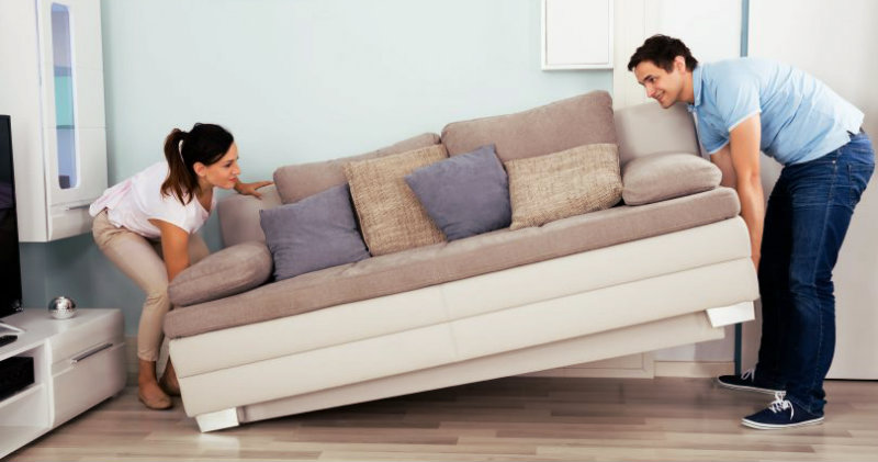 A couple lifting a sofa from the ground