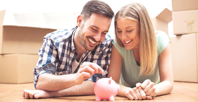 happy couple saving money in piggy bank