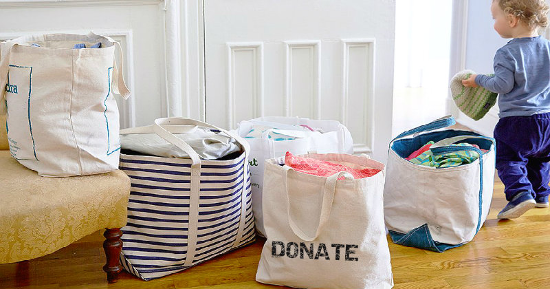 toddler standing near four bags filled with clothes and marked as donate