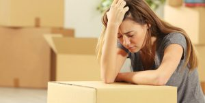 worried woman leaning on packed cardboard box