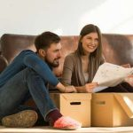 young couple sitting on the floor and planning for a house relocation