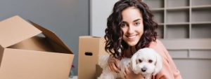 young woman preparing for a house relocation with her dog