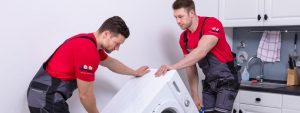 professionals trying to relocate a washing machine