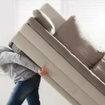 young man trying to move a couch alone